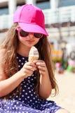 吃在海滩的小女孩孩子冰淇凌 夏天 免版税库存照片