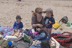 吃在海滩的小孩午餐 库存照片