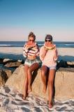 吃在海滩的愉快的女孩西瓜 友谊, happines 免版税图库摄影