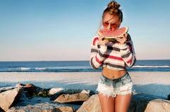 吃在海滩的愉快的妇女西瓜 免版税库存照片