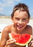 吃在海滩的男孩瓜 免版税库存图片