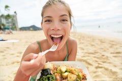 吃在海滩的滑稽的妇女沙拉健康膳食 库存图片