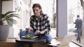 吃在清淡的咖啡馆的可爱的少妇午餐,享用她的沙拉,看膝上型计算机 正面图 影视素材
