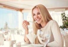 吃在清淡的夏天咖啡馆的正面少妇冰淇凌 免版税库存照片