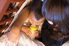 吃在瓶的亚裔逗人喜爱的婴孩牛奶 库存照片
