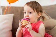 吃在生日聚会的愉快的女婴杯形蛋糕 免版税库存照片
