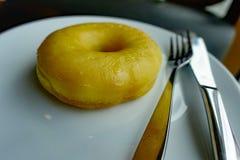 吃在白色盘的一个多福饼在黑背景中 免版税库存照片