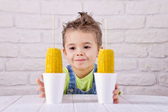 吃在白色砖墙backgroun的逗人喜爱的男孩煮沸的甜玉米 免版税库存图片