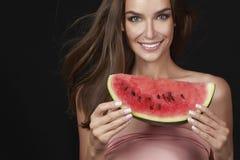 吃在白色背景的美丽的性感的深色的妇女西瓜,健康食物,鲜美食物,有机饮食,微笑健康, blac 免版税库存图片