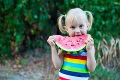 吃在绿色叶子背景的三岁的矮小的欧洲白肤金发的女孩一个西瓜  免版税库存图片