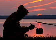 吃在罐外面的猎人在日落 免版税图库摄影
