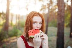 吃在自然的愉快的年轻女人西瓜 青年生活方式 幸福,喜悦,假日,海滩,夏天概念 免版税图库摄影