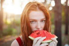 吃在自然的愉快的年轻女人西瓜 青年生活方式 幸福,喜悦,假日,海滩,夏天概念 库存图片