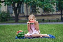 吃在草的逗人喜爱的小女孩西瓜在夏时 当马尾辫长的头发和暴牙的微笑坐草和enjo 免版税库存图片
