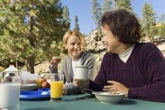 吃在营地的野餐桌上的妇女 库存照片