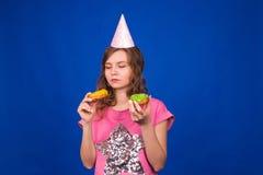 吃在蓝色背景的年轻美丽的妇女多福饼 不健康的饮食、速食和食物瘾概念 免版税库存图片