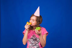 吃在蓝色背景的年轻美丽的妇女多福饼 不健康的饮食、速食和食物瘾概念 免版税图库摄影