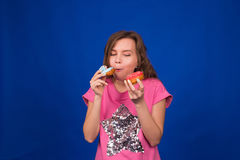 吃在蓝色背景的年轻美丽的妇女多福饼 不健康的饮食、速食和食物瘾概念 图库摄影