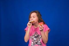 吃在蓝色背景的年轻美丽的妇女多福饼 不健康的饮食、速食和食物瘾概念 免版税库存照片