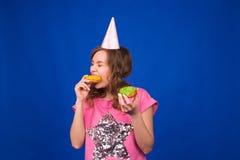 吃在蓝色背景的年轻美丽的妇女多福饼 不健康的饮食、速食和食物瘾概念 库存照片