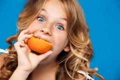 吃在蓝色背景的年轻俏丽的女孩桔子 免版税库存图片