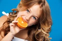 吃在蓝色背景的年轻俏丽的女孩桔子 图库摄影
