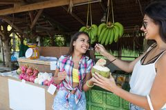 吃在街市上的愉快的妇女新鲜的椰子在泰国可爱的女孩游人在度假在亚洲 免版税图库摄影