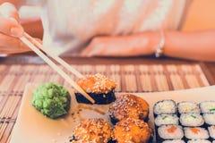 吃在街道咖啡馆的寿司 免版税库存照片