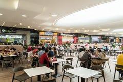 吃在豪华商城内部的餐馆的人们 库存图片