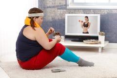 吃在运动装的肥胖妇女巧克力蛋糕 免版税库存照片