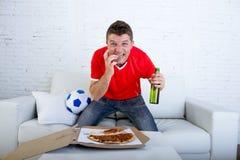 年轻吃在重音佩带的队球衣观看的橄榄球电视的人单独举行的啤酒瓶薄饼 免版税库存图片