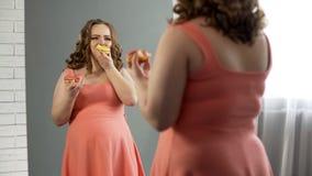 吃在镜子,营养混乱问题前面的不快乐的肥胖女性油炸圈饼 图库摄影