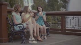 吃在长凳的三个美丽的女朋友冰淇凌 影视素材