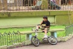 吃在长凳的孩子在Banos,厄瓜多尔 库存图片