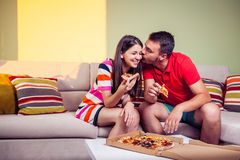 吃在长沙发的质朴的年轻夫妇薄饼 免版税库存照片