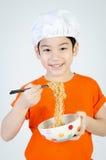 吃在陶瓷碗的亚裔孩子拉面面条。 免版税库存照片