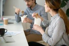 吃在面条箱子的办公室人中国食物在午餐期间 免版税图库摄影