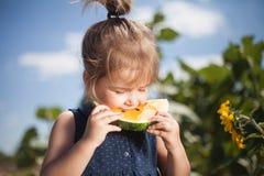 吃在领域的孩子黄色西瓜 免版税库存图片