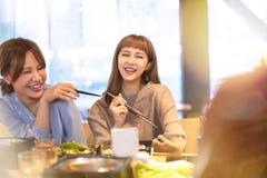 吃在餐馆的亚洲年轻小组 免版税库存照片