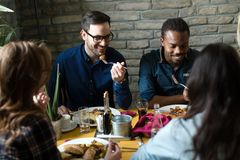 吃在餐馆的小组愉快的商人 免版税库存照片