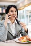 吃在餐馆的年轻女实业家 免版税库存图片
