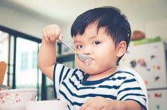 吃在高脚椅子的亚裔小孩男孩 库存照片