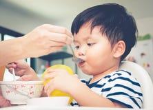 吃在高脚椅子的亚裔小孩男孩 库存图片