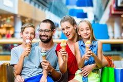 吃在购物中心的家庭冰淇凌与袋子 库存图片