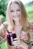 吃在绿色夏天户外背景的年轻愉快的女孩草莓酱 免版税库存图片