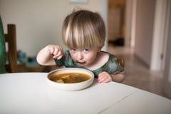 吃在kitch的可爱的白种人小孩男孩健康汤 图库摄影