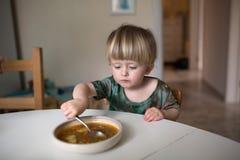 吃在kitch的可爱的白种人小孩男孩健康汤 免版税库存图片