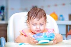 吃在sittting的厨房里的婴孩在桌上 库存图片