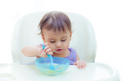 吃在sittting的厨房里的婴孩在桌上 免版税图库摄影