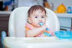 吃在sittting的厨房里的婴孩微笑在桌上 免版税库存图片